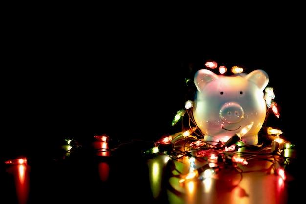 Синяя копилка с рождественскими гирляндами на празднике счастливого декабря. наслаждайтесь экономией, потратив деньги на концепцию праздника.