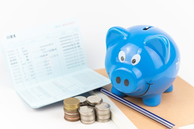 Blue piggy bank with coins pile on  book and account book white background