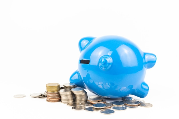 Blue piggy bank with coins pile on white background. finance savings and money wealth concept.