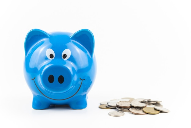 Blue piggy bank with coins pile on white background finance savings and money wealth concept
