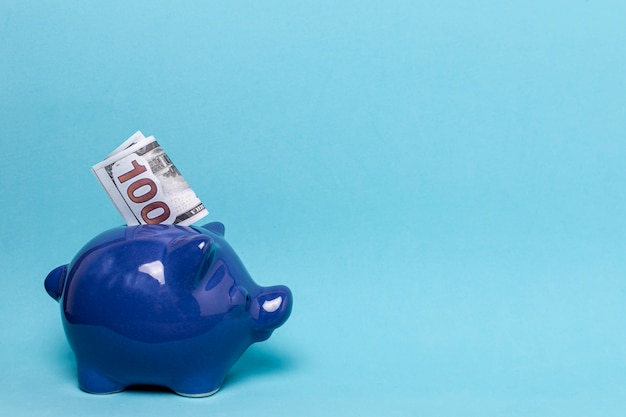 Blue piggy bank with copy space blue background