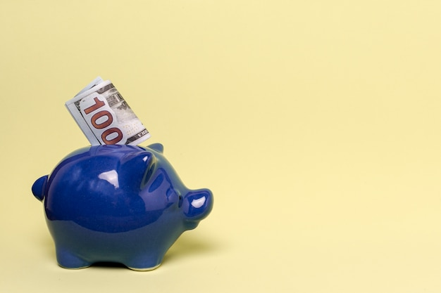 Blue piggy bank with copy space yellow background