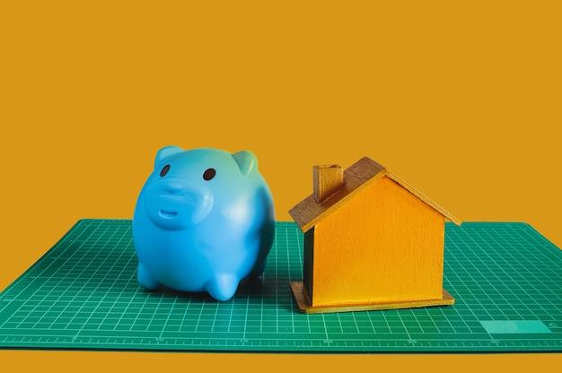 Blue piggy bank with golden house on green mat.