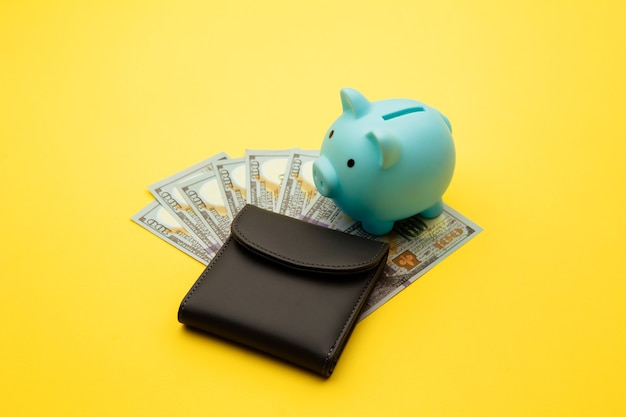 Blue piggy bank with a wallet with hundred-dollar bills on a yellow background. family budget, savings.