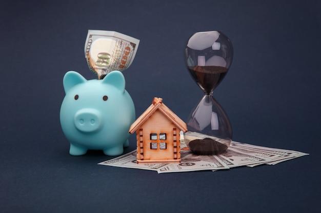 家の木製モデルと青い貯金箱