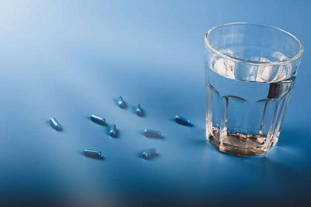 Капсулы синие таблетки со стаканом воды на синем фоне мягкий выборочный фокус