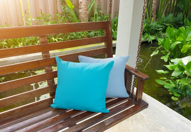 Blue pillow placed on a wooden swing in the resort.