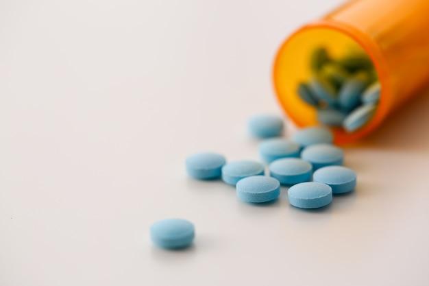 白い表面のパックからドロップされた青い錠剤