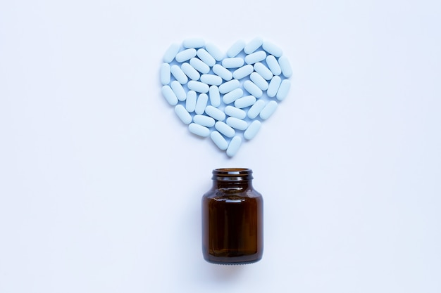 Blue pills forming a heart shape over bottle
