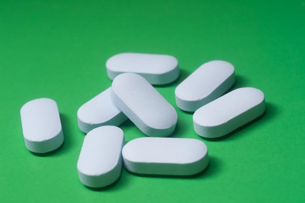 Blue pills on green background