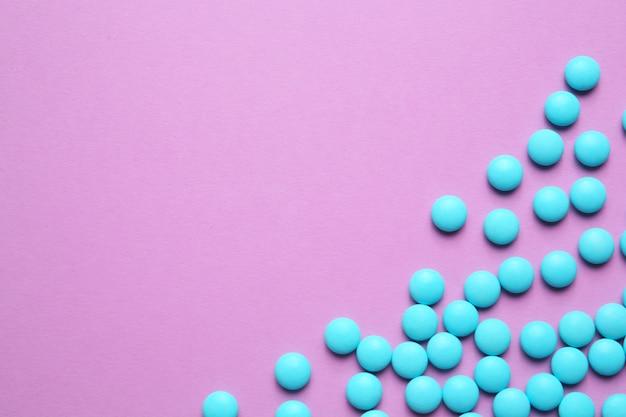 Синие таблетки на цветном фоне