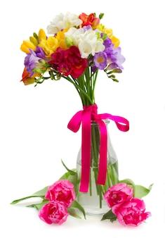白い背景で隔離のガラスの花瓶の青、ピンク、黄色のフリージアの花