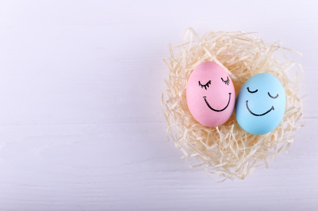 Blue and pink eggs with painted smiles in the nest, copy space. happy easter concept greeting card design.
