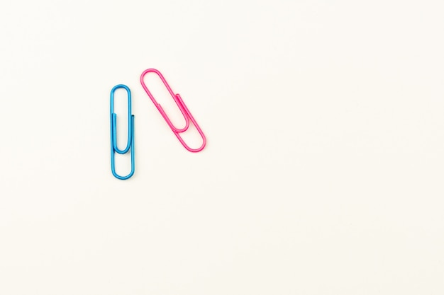 Blue and pink paper clips on white