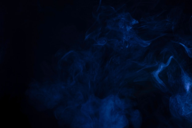 Blue and pink steam on a black surface. copy space.