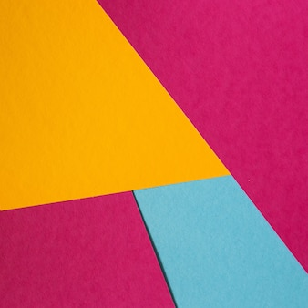 Blue, pink, yellow pastel color paper geometric flat lay background.