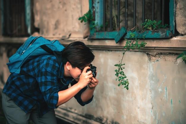 Blue plaid shirtのアジアの旅行者wで旅行するためのフィルムカメラで写真を撮る