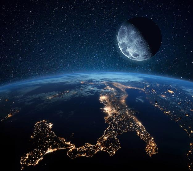 Голубая планета земля с огнями города в космосе на звездном небе с луной. луна с кратерами возле планеты. ночная жизнь италии и центральной европы