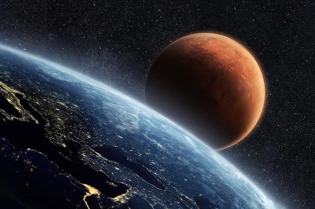 Голубая планета земля с огнями ночных городов, вид из космоса. красная планета марс в звездном небе. две планеты в космосе. путешествие с земли на марс, концепция