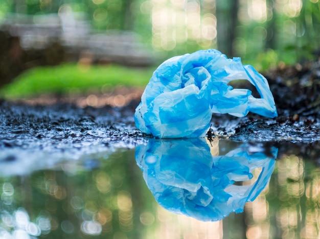 雨上がりの水たまりに映る、森に散らばる青いビニール袋。エコロジー、リサイクル、プラスチック汚染の概念。