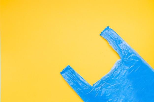 노란색 배경 복사 공간, 평면도에 파란색 비닐 봉투 프리미엄 사진