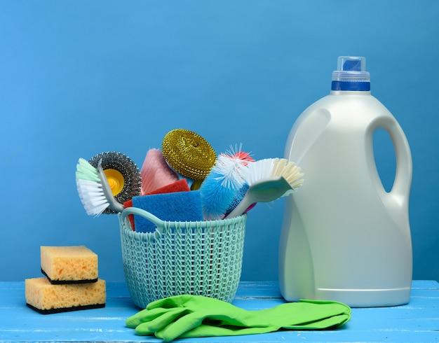 브러쉬, 스폰지, 청소용 고무 장갑, 파란색 배경과 파란색 플라스틱 바구니