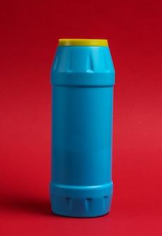 赤い背景のクリーニングのための粉末の青いプラスチックボトル。