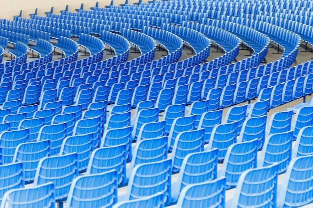 ビジネスプレゼンテーションのためにホールの円の周りに行に配置された青いプラスチックの椅子