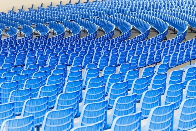 Blue plastic chairs arranged in rows around the circle in the hall for business presentations