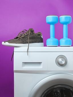 青いプラスチック製のダンベルと紫色の表面に対して洗濯機のスポーツシューズ