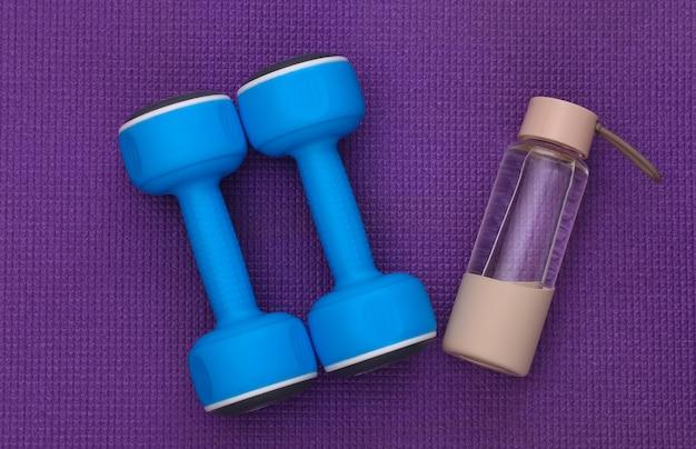 紫色の背景に青いプラスチック製のダンベルと水筒。上面図