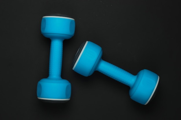 Blue plastic dumbbells on a black background. top view