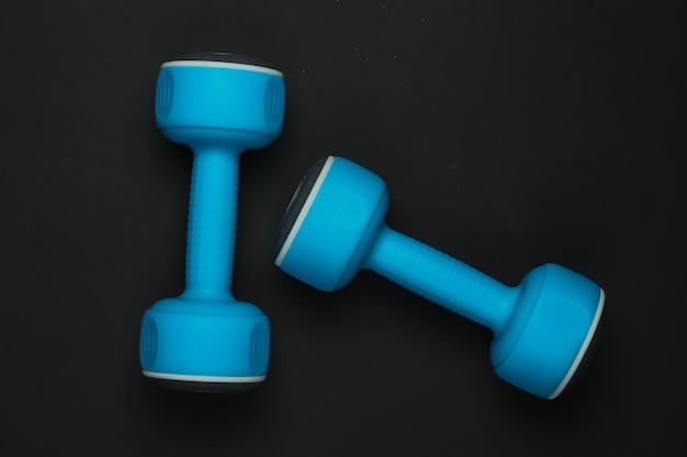 黒の背景に青いプラスチック製のダンベル。上面図