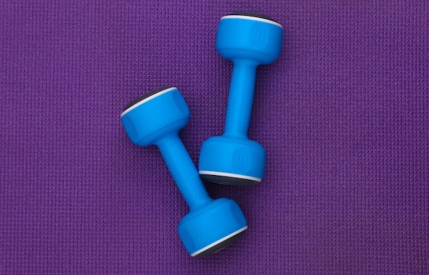 Blue plastic dumbbells on a purple background. top view