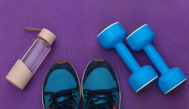 青いプラスチック製のダンベル、スポーツシューズ、紫色の背景に水筒。上面図。フラットレイ
