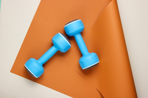 Blue plastic dumbbells on wrapped paper