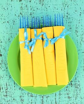 緑に黄色い紙ナプキンに包まれた青いプラスチック フォーク