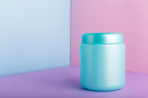 コピースペースとピンク色の背景に化粧品のモックアップと青いプラスチック製の瓶。ヘアマスク、コンディショナーシャワージェル衛生製品、自家製自然化粧品の化粧品パッケージ。