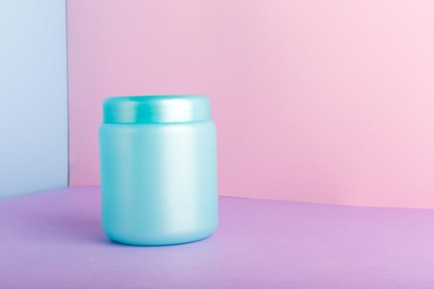 Синяя пластиковая банка с макетом для косметических продуктов на цветном розовом фоне с копией пространства. косметическая упаковка для волос, маска, кондиционер, гель для душа, средства гигиены, домашняя натуральная косметика.
