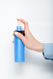Blue plastic spray for cosmetics in a female hand