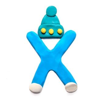 Синяя пластилиновая буква x алфавита в зимней шапке на белом фоне