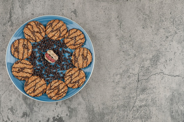 Blue plate of biscuits, drop chocolate and peanuts on marble background.