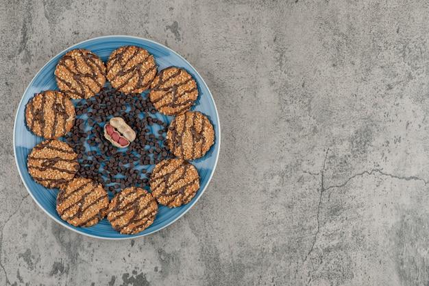 Piatto blu di biscotti, gocce di cioccolato e arachidi su sfondo marmo.