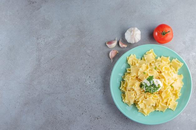 Piatto blu di pasta bollita deliziosa su fondo di pietra.