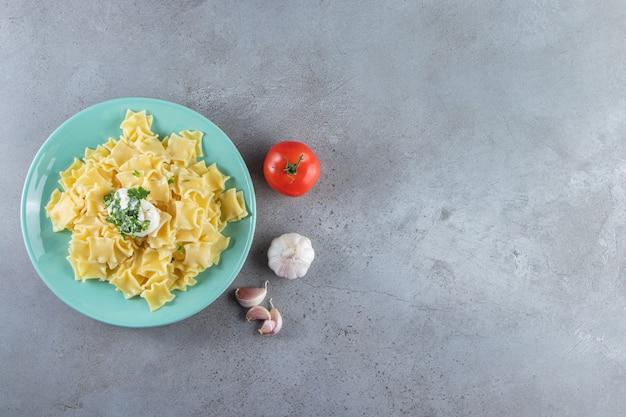 Piatto blu di deliziosa pasta bollita su fondo di pietra.