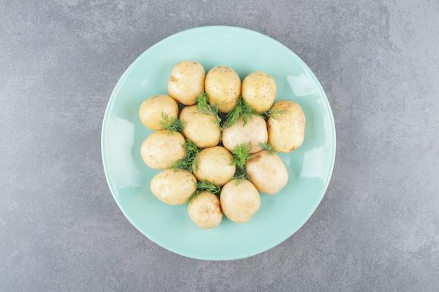 Un piatto blu di patate bollite con aneto fresco