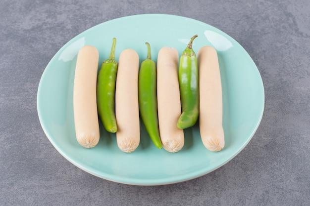 Un piatto blu di salsicce bollite con peperoncino