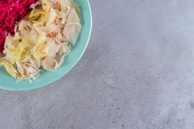 Piatto blu di varietà di crauti di cavolo cappuccio sul tavolo di pietra.