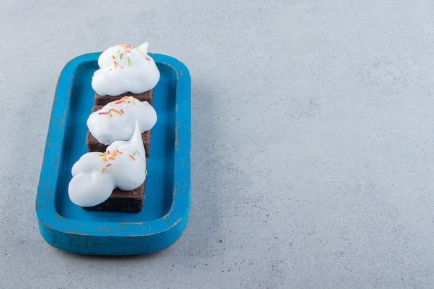 Un piatto blu di biscotti al cioccolato con granelli colorati e panna. foto di alta qualità