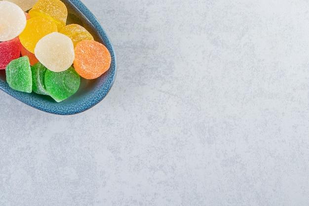 Piatto blu di marmellate di gelatina colorate su sfondo marmo.